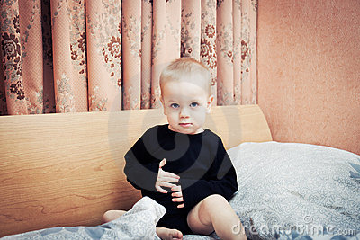 Baby boy posing on parents  bed in bedroom