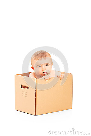 Baby boy sitting in a cardboard box