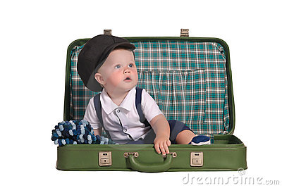 Baby boy sitting in green suitcase