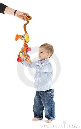 Baby boy standing with toy