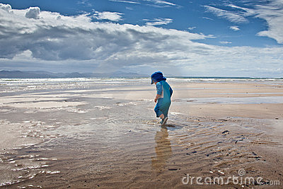 Baby boy walking on large beach