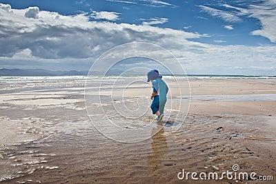 Baby boy walking on large beach