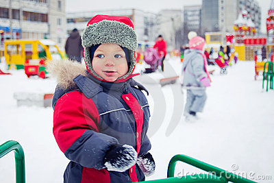 Baby boy on a winter playground