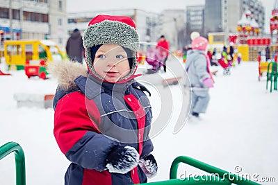 Baby boy on a winter playground