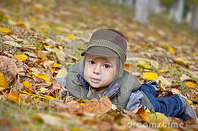 Baby boy among yellow fallen leaves