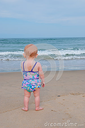 Baby Child on Beach Stares at Ocean