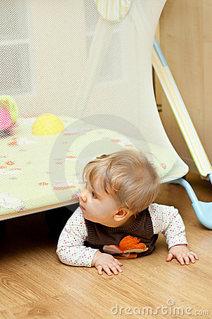 Baby crawling under playpen