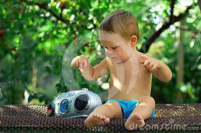 Baby DJ playing with retro recorder in garden