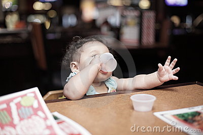 Baby drinking at a table