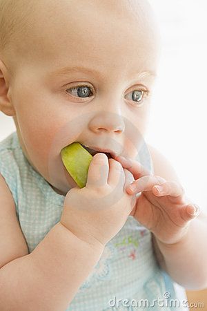 Baby eating apple indoors