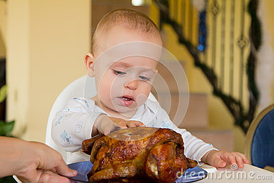 Baby eating a big grilled chicken
