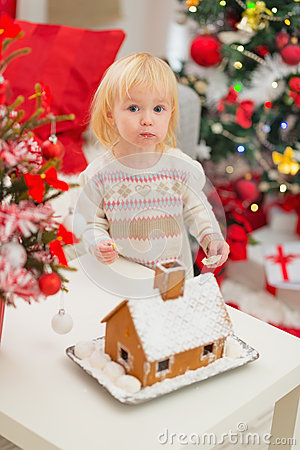 Baby eating cookies near Gingerbread house