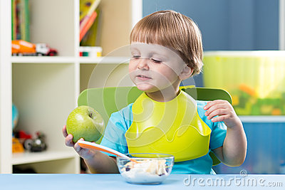 Baby eating healthy food. Stock Photo