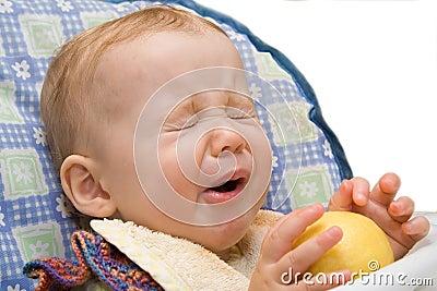 Baby eating lemon on isolated background