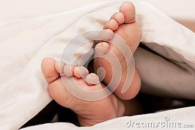 Baby feet under a blanket