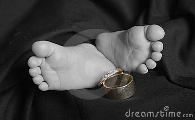 Baby feet with wedding rings selective color
