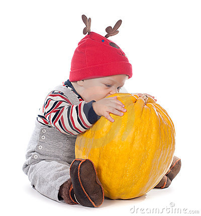 Baby in funny deer hat with orange pumpkin