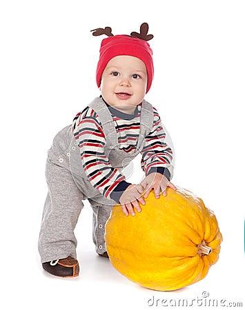 Baby in funny deer hat with orange pumpkin