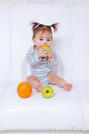 Baby girl biting an apple