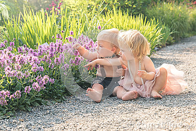 Baby girl and boy sitting in a beautiful garden and pointing to purple flower Stock Photo