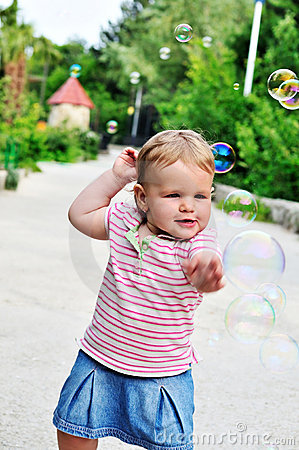 Baby girl catching soap bubbles
