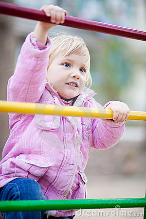 Baby girl on child s playground in spring time