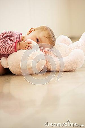 Baby Girl Cuddling Pink Teddy Bear At Home