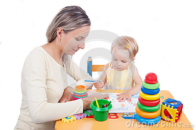 Baby girl drawing with her mother