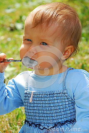Baby girl eating by herself outdoor