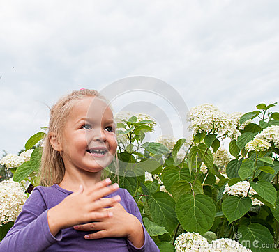 Baby girl fun playing in white flowers