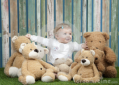 Baby girl with group of teddy bears, seated on grass