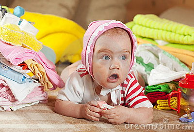Baby girl with heap of baby s wear