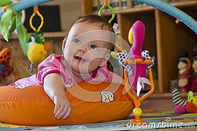 happy Baby girl toy lying tummy