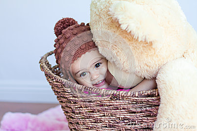 Baby girl hugging big teddy bear in basket