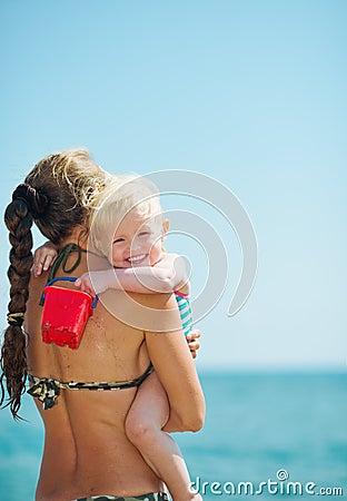 Baby girl hugging mother on beach