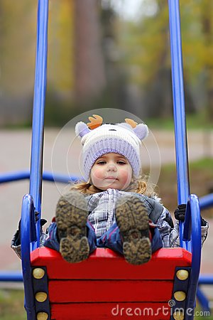 Free Baby Girl In A Funny Hat Swinging On The Winter Playground, Perspective Point Of View. Stock Image - 103398801