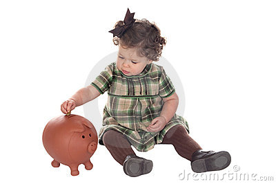 Baby girl inserting a coin into a piggybank