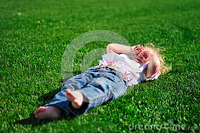 Baby girl laying on the green grass in the park