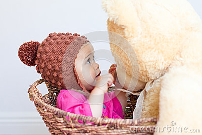 Baby girl looks at face of teddy bear