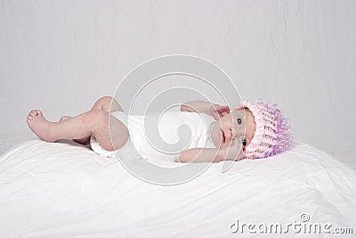 Baby girl lying on bed