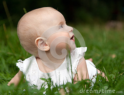 Baby girl lying on grass
