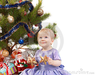 Baby girl make a wish under Christmas tree