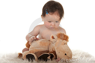 Baby girl observing stuffed animal horse