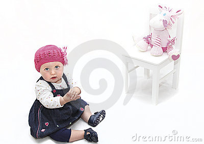 Baby girl in pink hat and toy