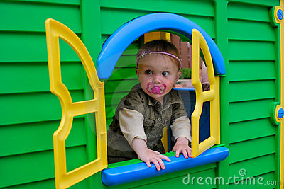 Baby girl in playhouse window