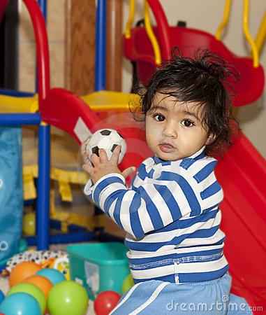 Baby Girl Playing with Balls in a Play Area
