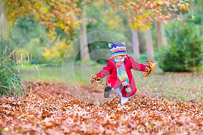 Baby girl playing with golden leaves in autumn park