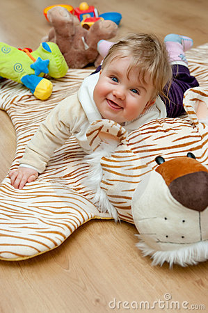 Baby girl playing on tiger rug