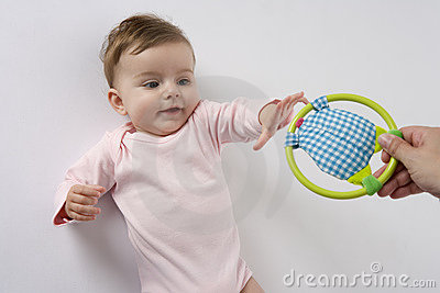 Baby girl reaching for toy