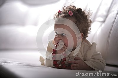 Baby girl with red beads in profile